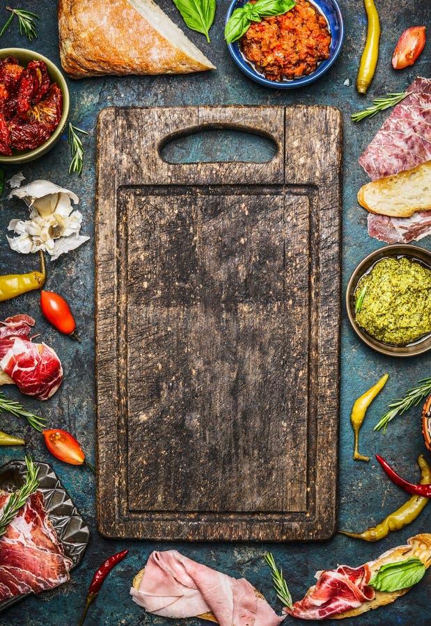 bruschetta或crostini做的各种各样的成份:熏制的肉,香肠,火腿, pesto,干蕃茄,在空白的老c附近的意大利辣味香肠 免版税库存照片