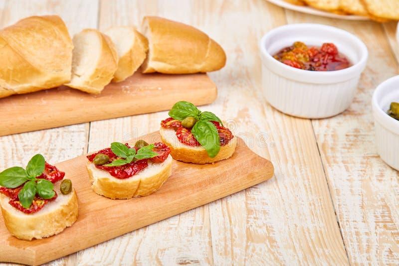 Bruschetta或crostini用各式各样的蕃茄和雀跃在一个木厨房板有木背景 新意大利语 库存图片