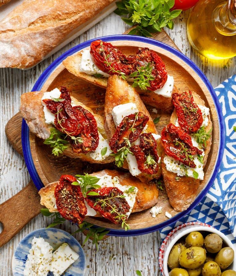 Bruschetta用希腊白软干酪,干蕃茄,橄榄油和新鲜的芳香草本,在一块板材在一张木桌上,顶视图 免版税库存照片