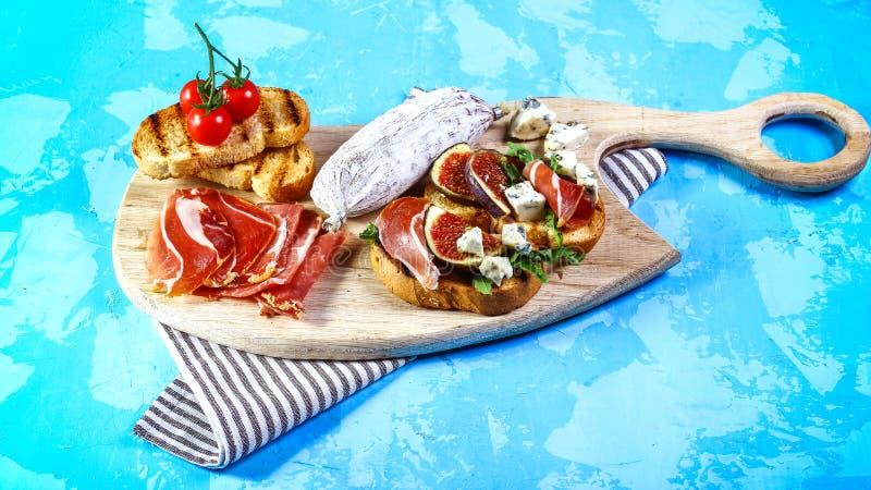 Bruschetta用意大无花果用乳酪,西红柿 意大利开胃菜 平的位置 顶视图 地道生活方式图象 免版税图库摄影