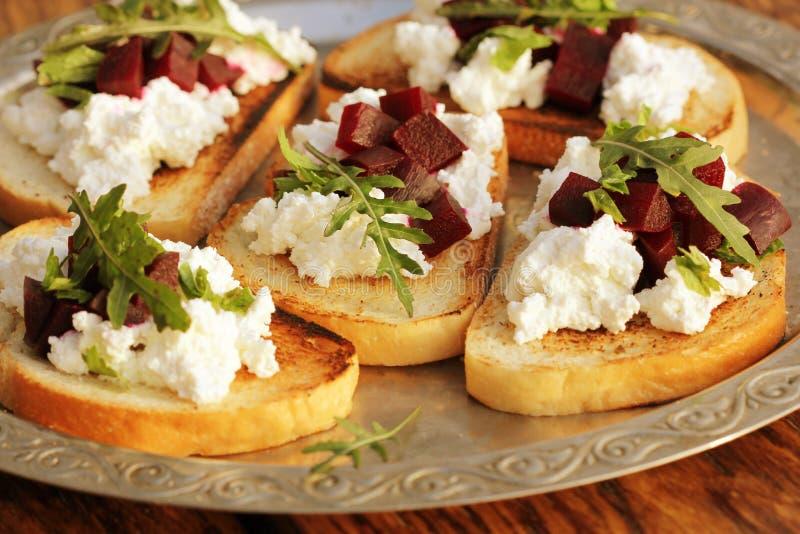 Bruschetta用甜菜、希脂乳和ruccola 库存照片