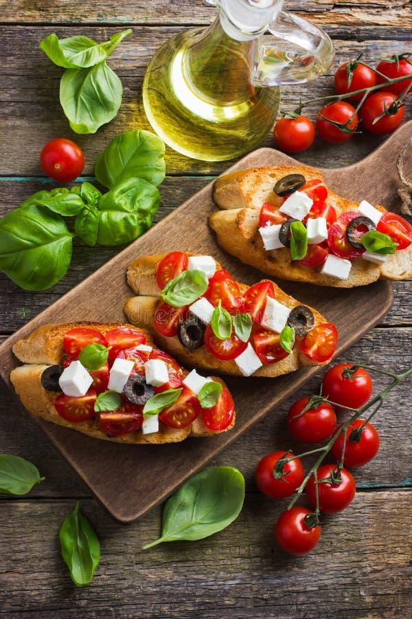 Bruschetta用蕃茄、希腊白软干酪和蓬蒿 免版税库存照片