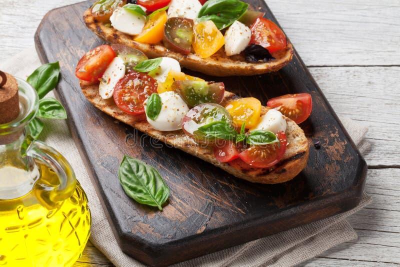 Bruschetta用蕃茄、无盐干酪和蓬蒿 免版税库存照片