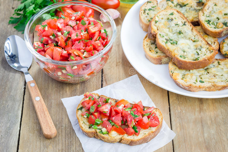 Bruschetta用蕃茄、草本和油在敬酒的乳酪面包 免版税库存照片