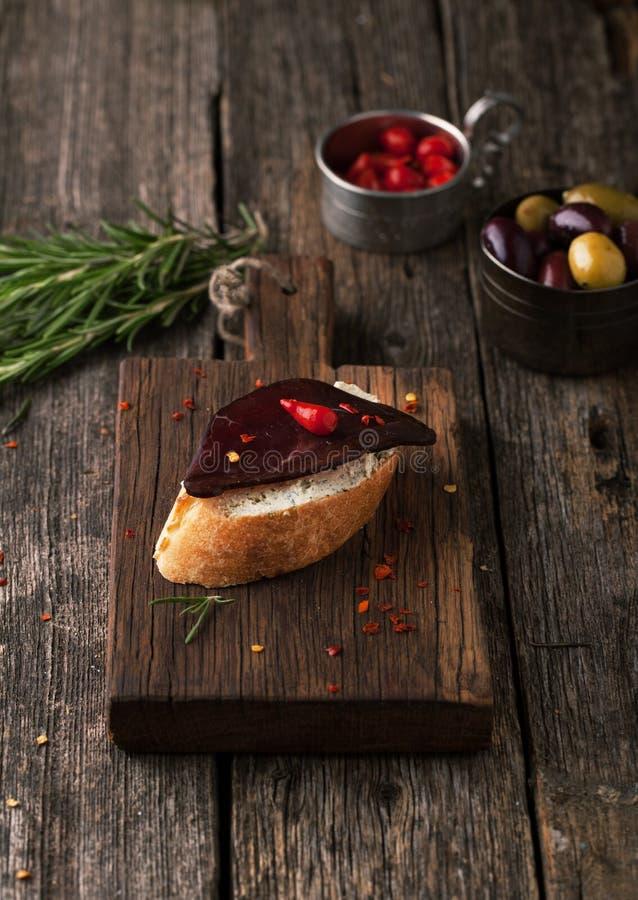 Bruschetta με καπνισμένες το βόειο κρέας κρέας, τα τσίλι, το δεντρολίβανο και τις ελιές στοκ φωτογραφία με δικαίωμα ελεύθερης χρήσης