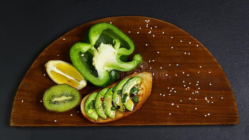 Bruschetta, σάντουιτς με το αβοκάντο, το ακτινίδιο, το λεμόνι και το πράσινο πιπέρι στον ξύλινο πίνακα, σε έναν σχιστόλιθο, την έ στοκ φωτογραφίες