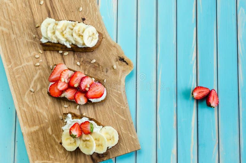 Bruschetta с рикоттой, клубникой и бананом сыра на деревянной предпосылке стоковое изображение