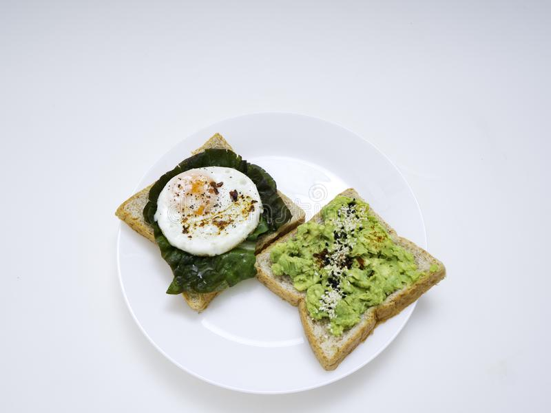 Bruschetta apetitoso con el huevo y el aguacate en una placa fotografía de archivo