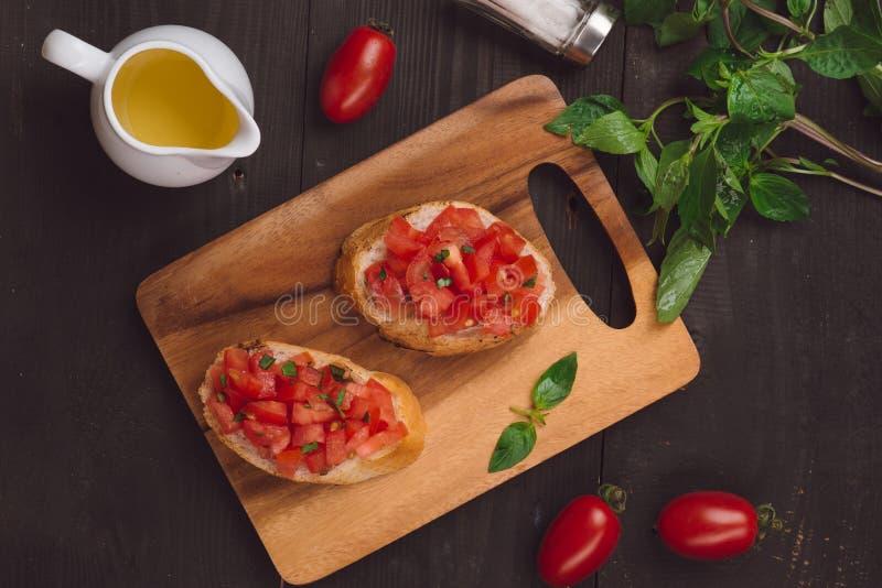 Bruschetta apetitoso italiano simples com tomate, no tabl de madeira imagens de stock royalty free