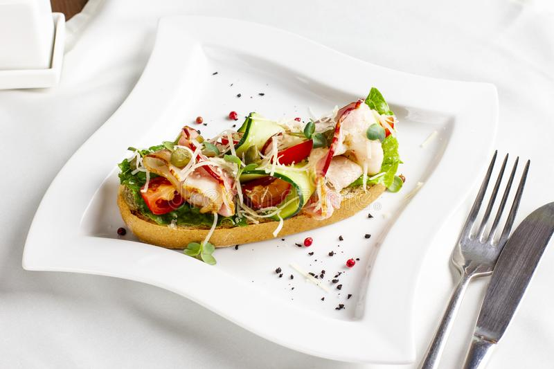 Bruschetta with bacon, fresh vegetables and capers on white plate royalty free stock photo