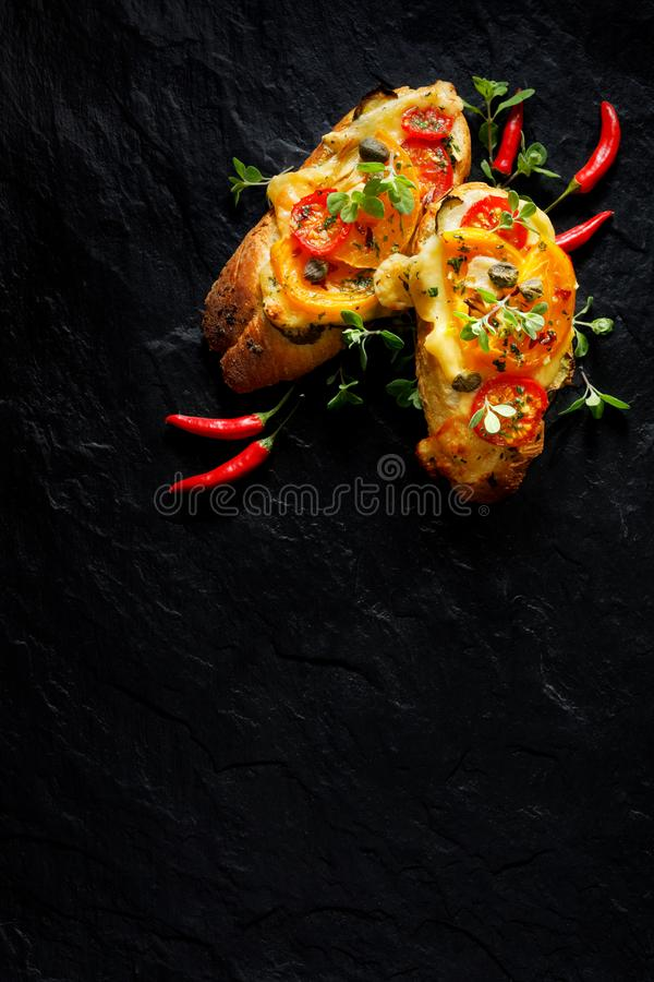 Bruschetta, baguette asado a la parrilla con la adición de tomates, de queso y de hierbas en un fondo negro, visión superior imágenes de archivo libres de regalías