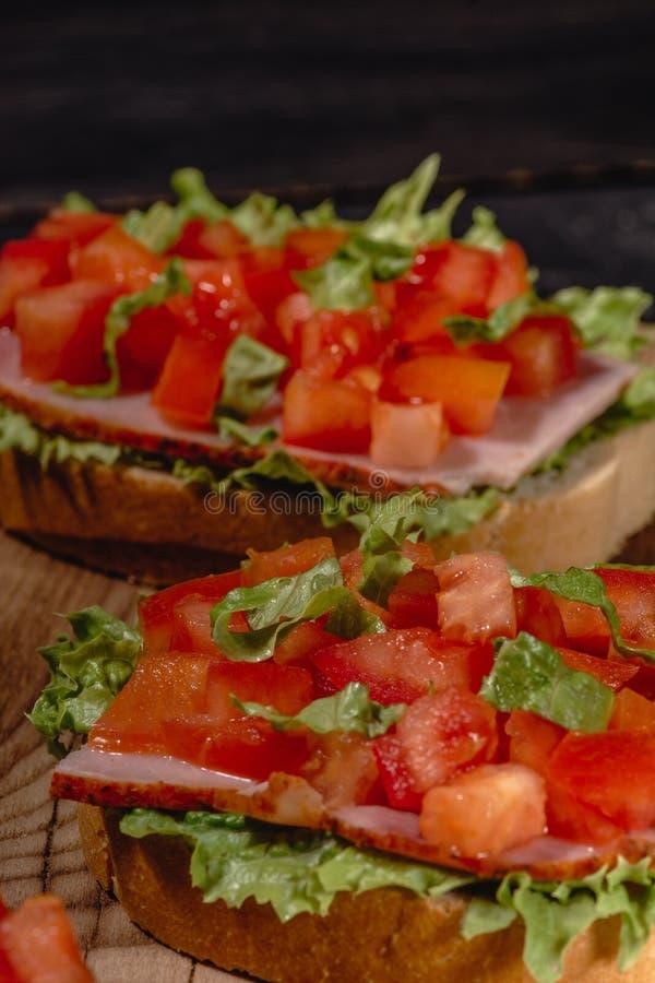 与切好的菜、草本和油的意大利蕃茄bruschetta在烤或敬酒的有壳的ciabatta面包 库存图片