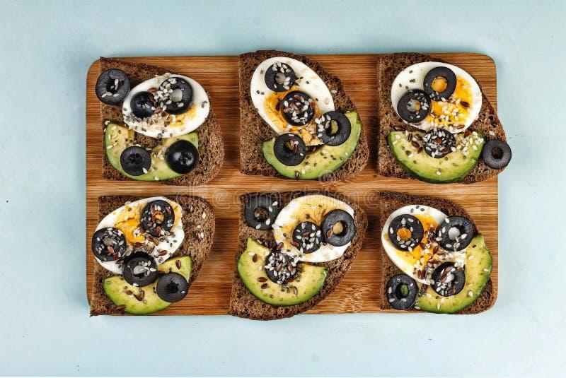 Bruschetta com abacate e azeitonas Alimento útil, petisco saudável imagem de stock