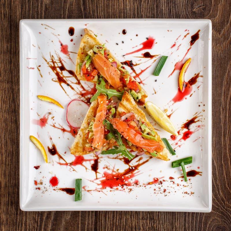 Bruschetta con el aguacate y el tomate del guacamole de la salsa con el salmón ahumado foto de archivo