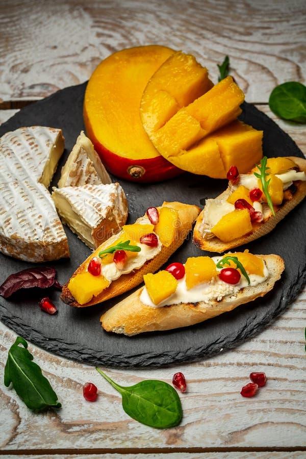 Bruschetta con el mango, el queso del camembert y la granada en una tabla rústica vieja Aperitivo o bocado italiano tradicional,  fotos de archivo libres de regalías
