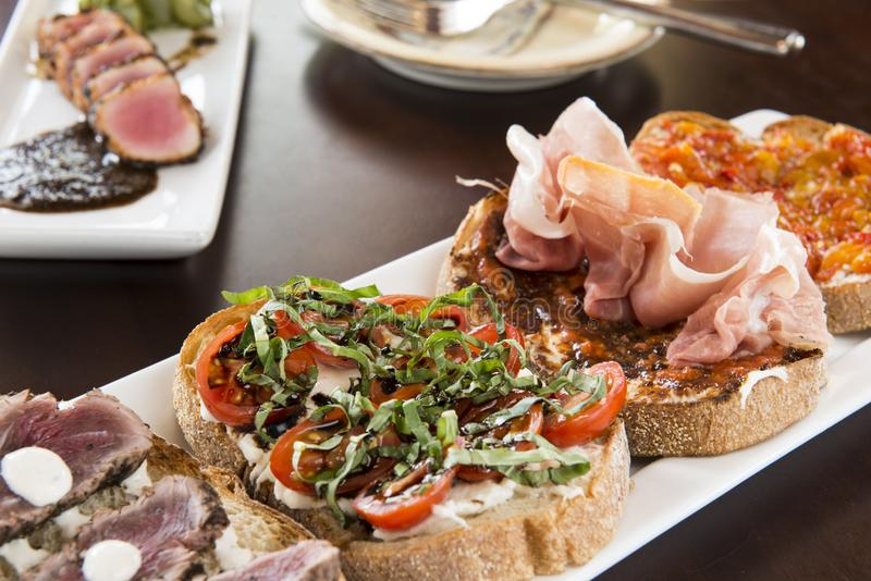 Bruschetta con el queso cremoso, carne, tomates fotos de archivo libres de regalías