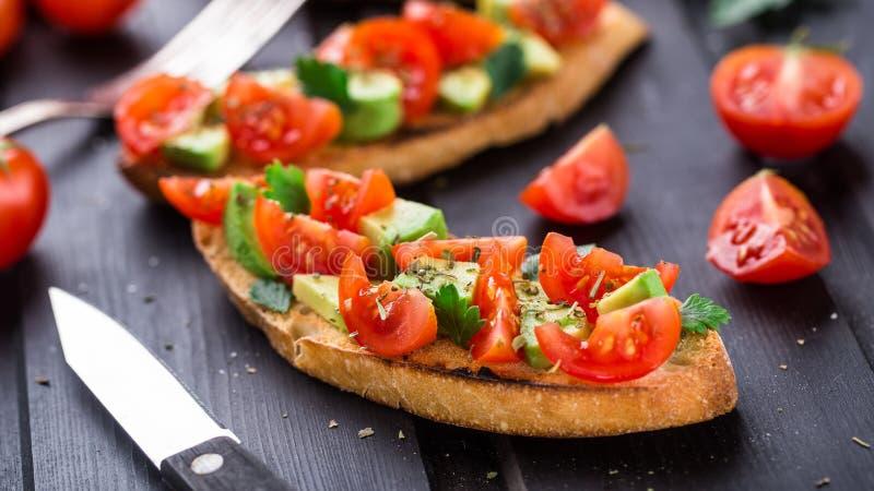 Bruschetta con el tomate, el aguacate y las hierbas fotografía de archivo libre de regalías