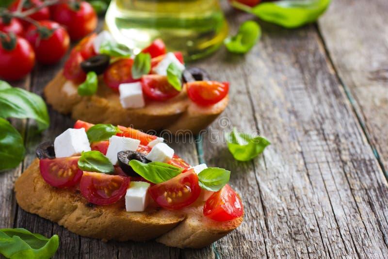 Bruschetta con el tomate, el queso feta y la albahaca fotos de archivo
