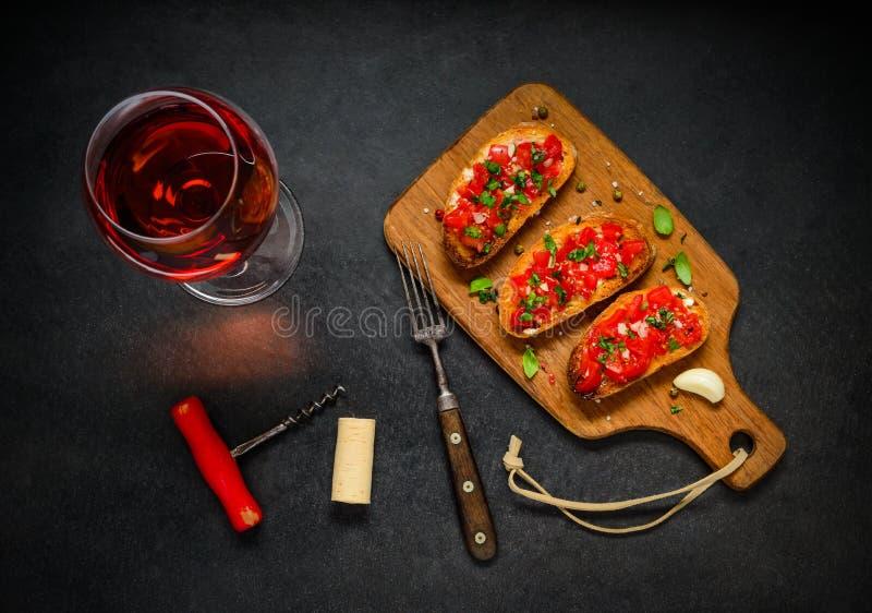Bruschetta con el tomate, la albahaca y Rose Wine imágenes de archivo libres de regalías