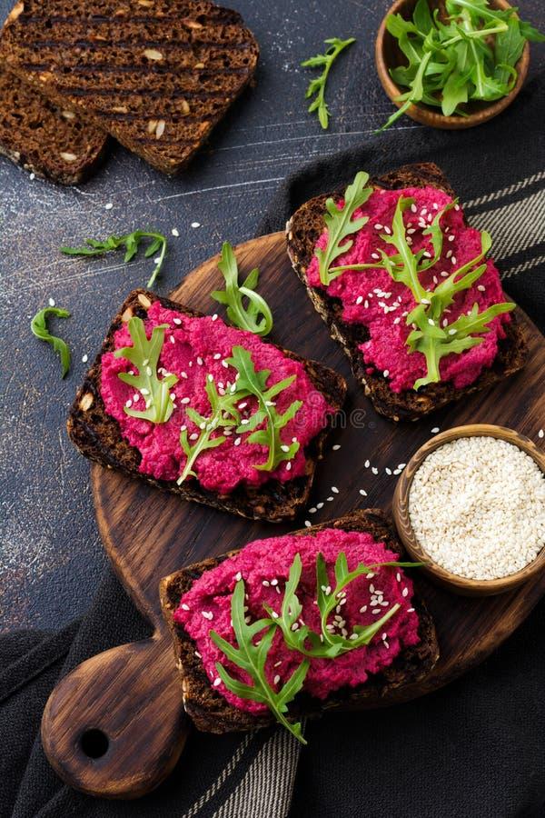 Bruschetta con hummus de las remolachas, arugula y semillas de sésamo en fondo concreto oscuro imagenes de archivo
