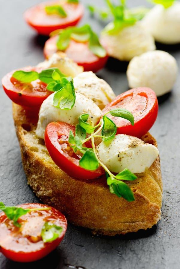 Bruschetta con i pomodori ciliegia e la mozzarella fotografia stock libera da diritti