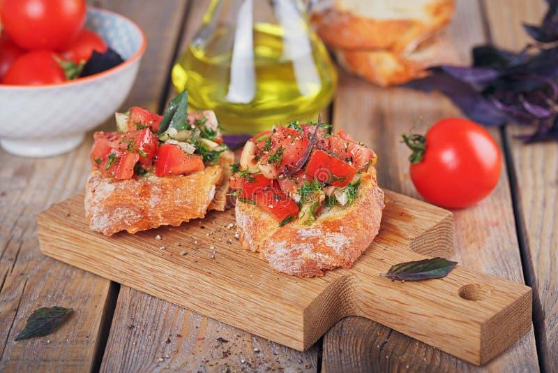 Bruschetta con i pomodori, il basilico e le erbe tagliati sul cru arrostito fotografia stock
