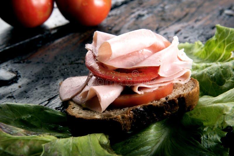 Bruschetta con il prosciutto ed il pomodoro della carne di maiale fotografie stock libere da diritti