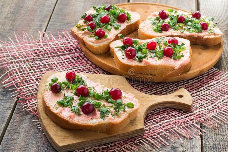 Bruschetta con la mantequilla, el caviar del capelín, el arándano y ella de color salmón foto de archivo libre de regalías