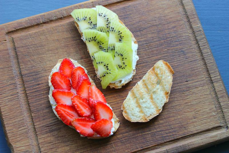 Bruschetta con la ricotta e le fragole e le bacche fresche del kiwi sull'intero pane tostato del grano immagine stock libera da diritti