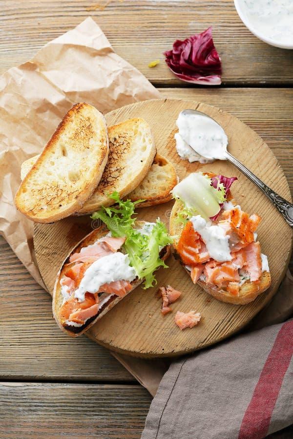 Bruschetta con la salsa y los salmones a bordo fotografía de archivo