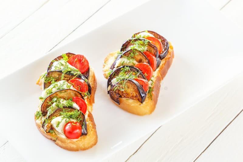 Bruschetta con las berenjenas fritas, los tomates frescos y el queso de la mozzarella en una placa imagenes de archivo