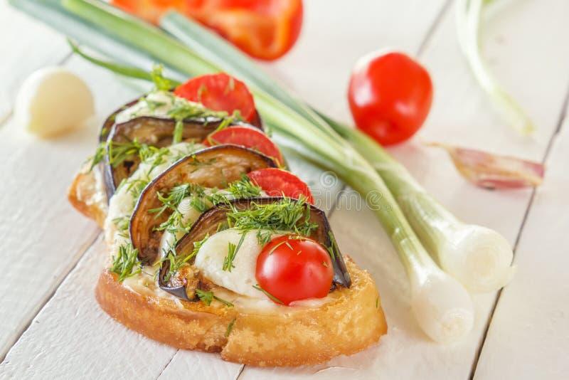 Bruschetta con las berenjenas fritas, los tomates frescos y el queso en los tableros blancos contra la perspectiva de verduras fr imagen de archivo