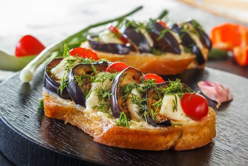 Bruschetta con las berenjenas fritas, los tomates frescos y el queso en tableros negros contra la perspectiva de verduras frescas fotos de archivo libres de regalías