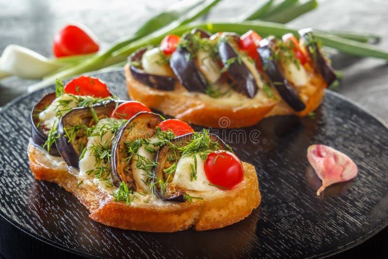 Bruschetta con las berenjenas fritas, los tomates frescos y el queso en tableros negros contra la perspectiva de verduras frescas imágenes de archivo libres de regalías
