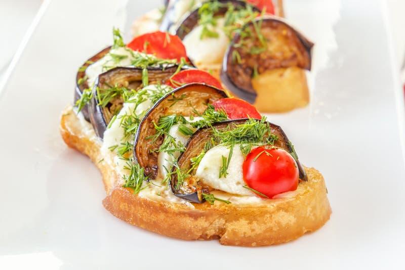 Bruschetta con las berenjenas fritas, los tomates frescos y el queso en una placa blanca fotos de archivo libres de regalías