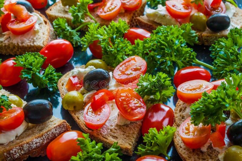 Bruschetta con le olive verdi e nere, il feta, i pomodori ciliegia, il prezzemolo ed il peperone su fondo nero immagine stock
