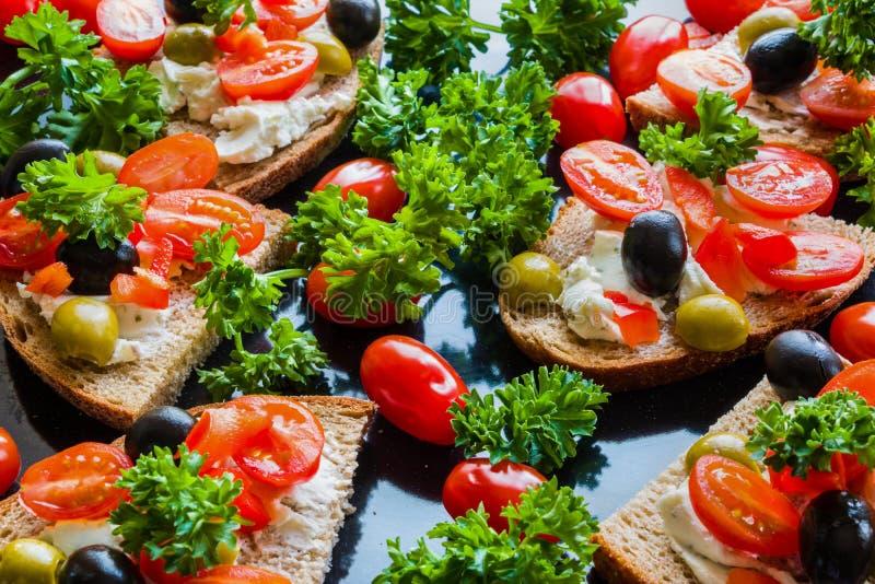 Bruschetta con le olive verdi e nere, il feta, i pomodori ciliegia, il prezzemolo ed il peperone su fondo nero immagine stock libera da diritti