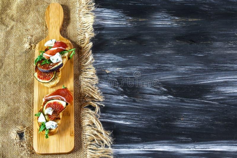 Bruschetta con los higos del jamón de prosciutto con queso Aperitivo italiano Endecha plana Visión superior Imagen auténtica de l foto de archivo
