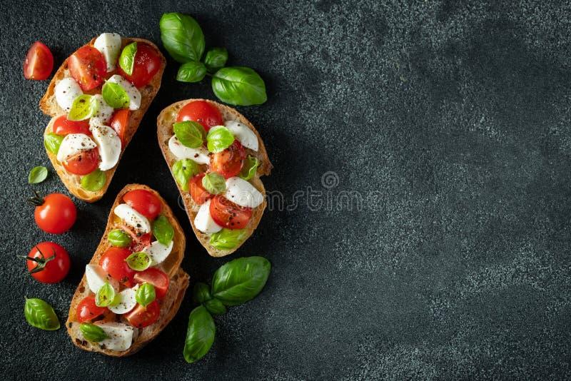 Bruschetta con los tomates, el queso de la mozzarella y la albahaca en un fondo oscuro Aperitivo o bocado italiano tradicional, a fotografía de archivo libre de regalías