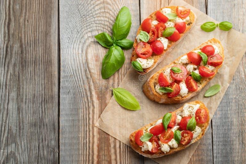 Bruschetta con los tomates, el queso de la mozzarella y la albahaca en una tabla rústica vieja Aperitivo o bocado italiano tradic imágenes de archivo libres de regalías