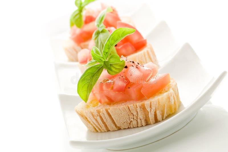 Bruschetta con los tomates y la albahaca aislados imagen de archivo libre de regalías