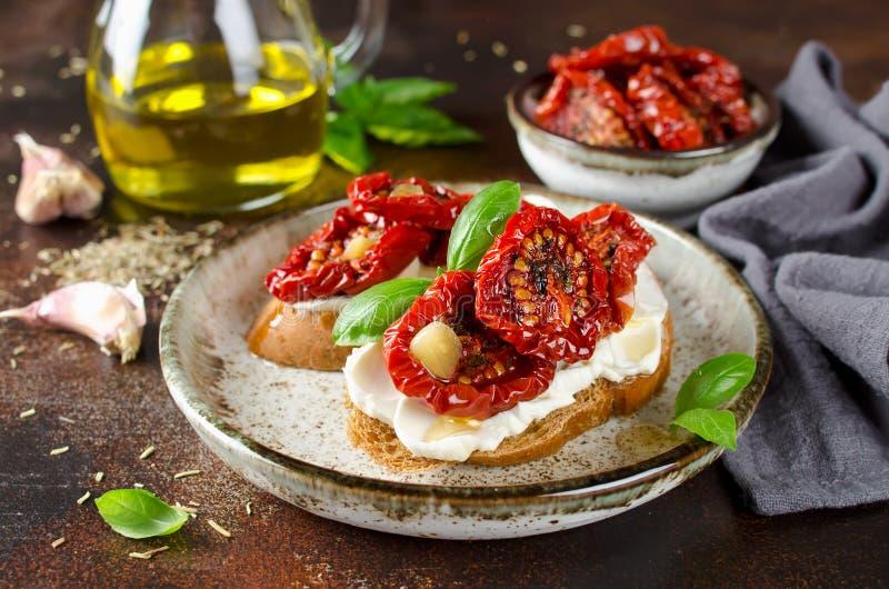 Bruschetta con olio d'oliva, i pomodori seccati al sole, la ricotta ed il basilico fresco fotografia stock libera da diritti