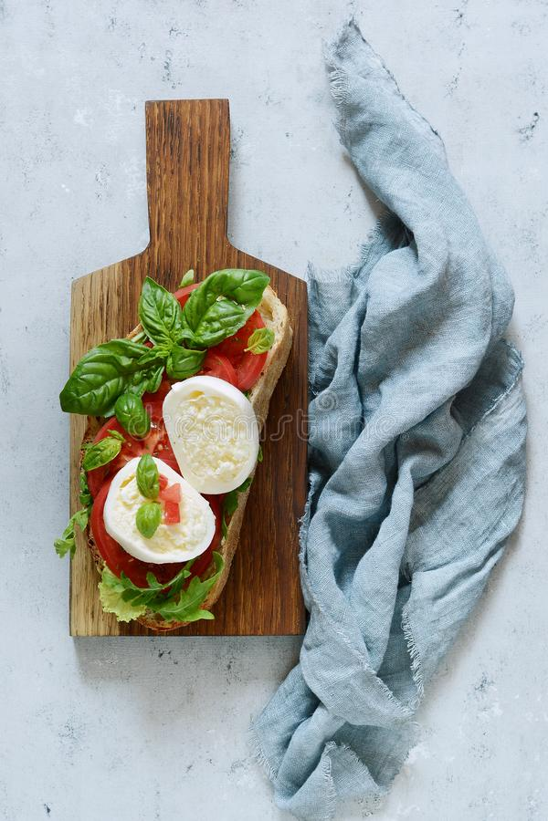 Bruschetta con queso del búfalo de la mozzarella en un tablero de cena de madera con las hojas de la salsa del tomate del arugula fotos de archivo libres de regalías