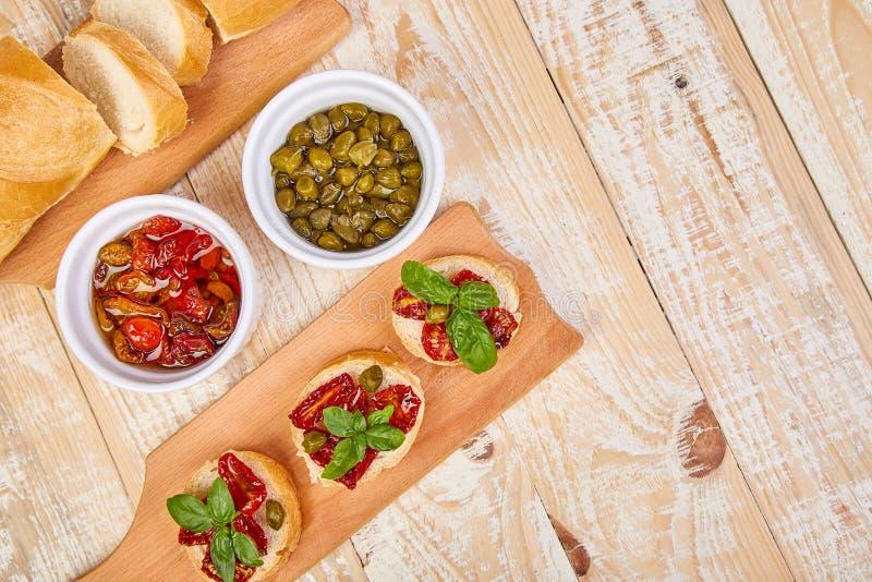 Bruschetta of crostini met in de zon gedroogde tomaten en kappertjes op een houten keuken scheept met houten achtergrond in Het v stock afbeelding