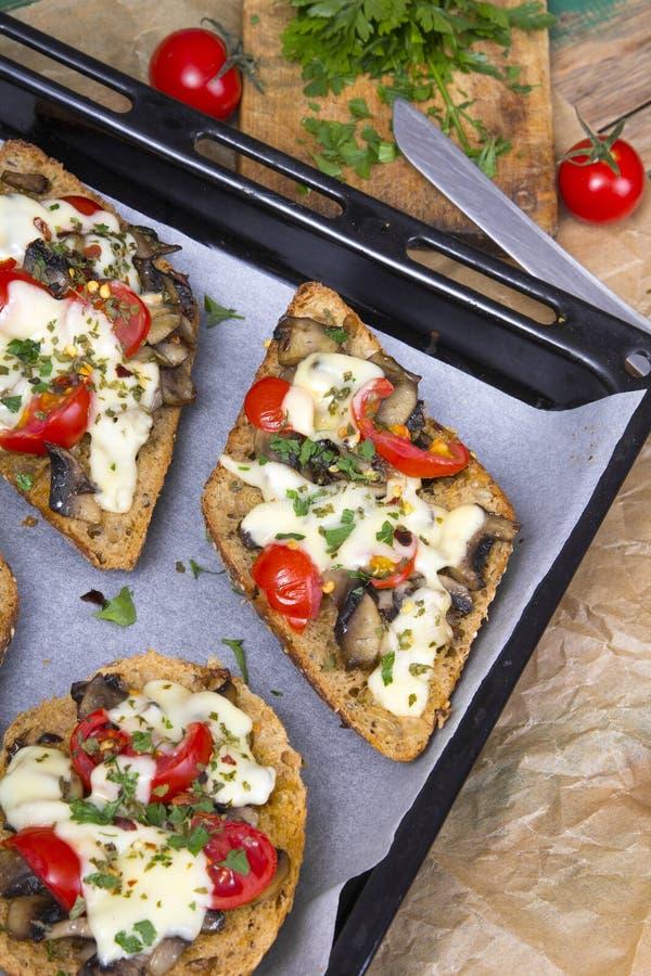 Bruschetta delicioso con los tomates, el queso y las setas imagen de archivo libre de regalías