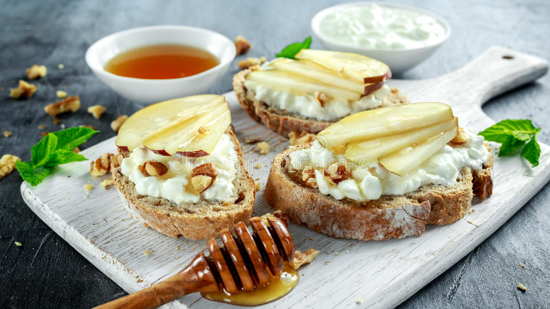 Bruschetta dell'aperitivo con la pera, il miele, la noce e la ricotta sul bordo bianco immagine stock