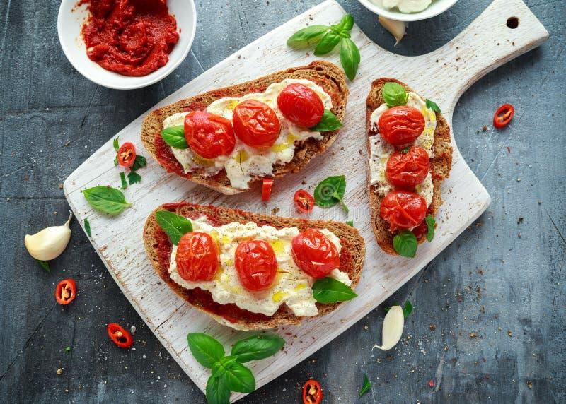 Bruschetta di ricotta del pomodoro con la pasta di pomodori, il pane nero dell'olio d'oliva ed il basilico seccati al sole in un  fotografia stock