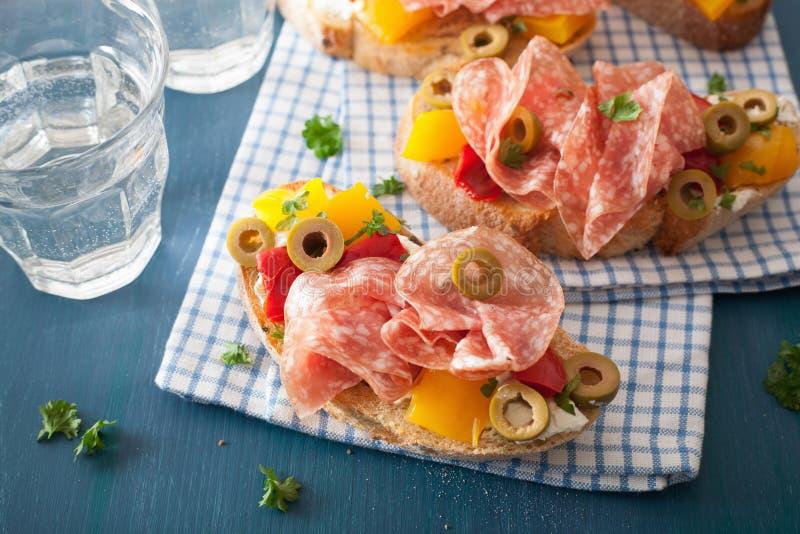 Bruschetta do salame com azeitonas roasted do queijo de cabra das pimentas imagem de stock royalty free