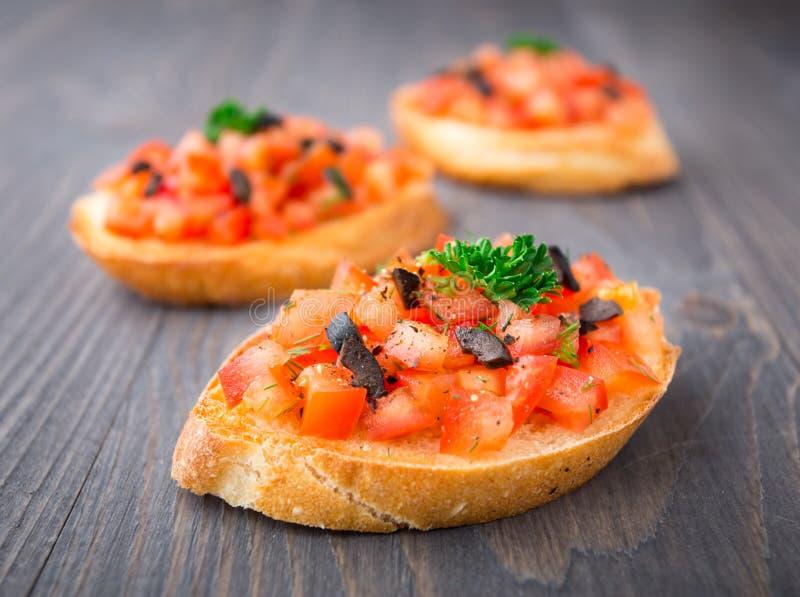 Bruschetta do tomate coberto com azeitona fotos de stock royalty free