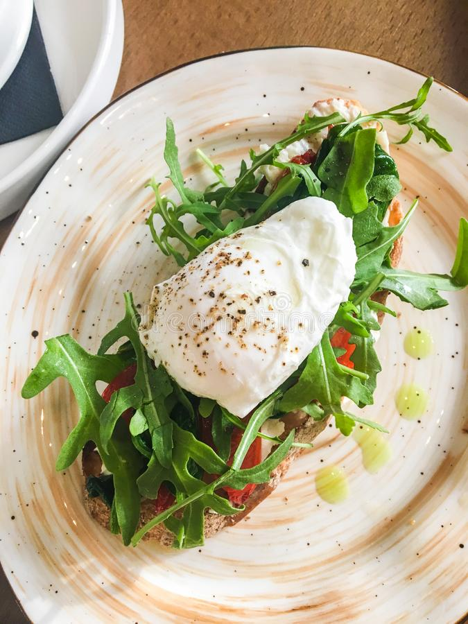 Bruschetta em uma placa em um caf? com tomates e ovo escalfado da r?cula imagem de stock